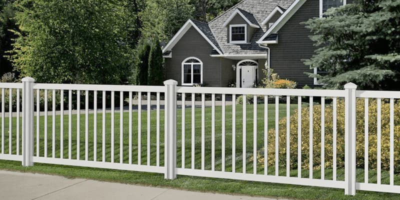 Fencing Calculator - charcoal gray traditional house with white vinyl fence in front yard
