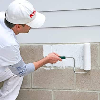 Applying KILZ Primer with roller to unpainted masonry wall