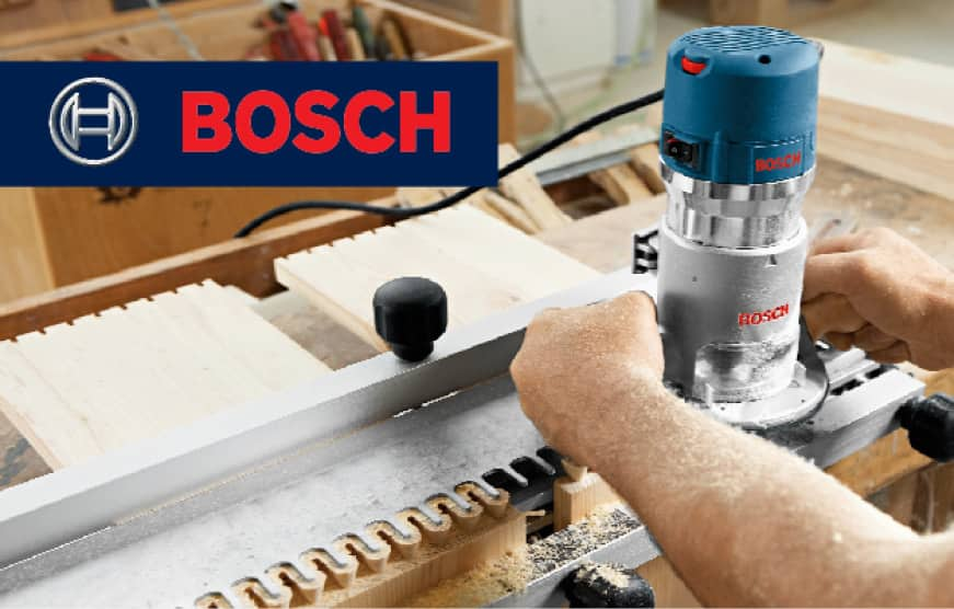 Hands holding Bosch router in use.