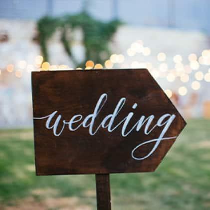 "Arrow-shaped chalkboard sign that reads ""Wedding"""
