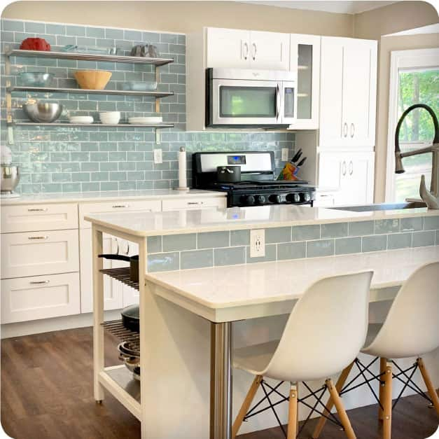 An elegant and modern kitchen with white cabinets which features a tiled backsplash of the Merola Tile 3-inch by 6-inch Chester Acqua Subway Tile