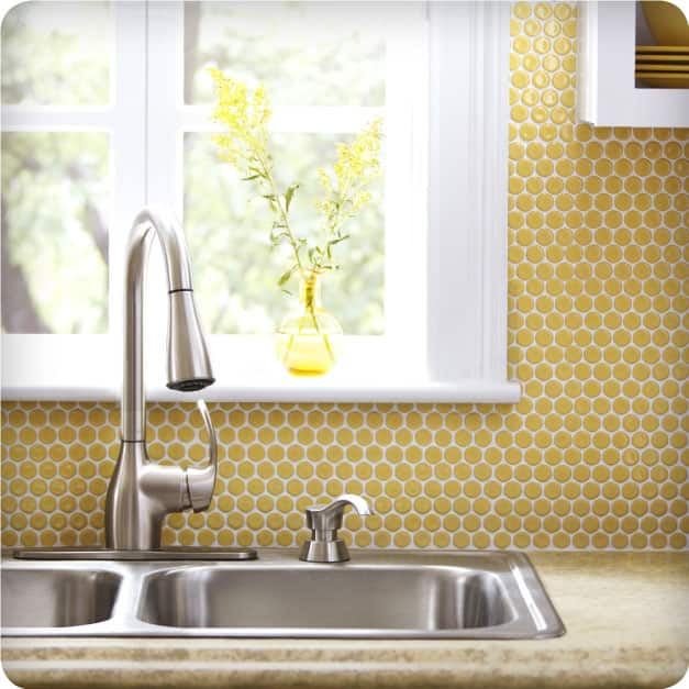 A close-up of a kitchen sink and counter featuring a tiled backsplash with the Merola Tile Hudson Penny Round porcelain mosaic tile in Vintage Yellow.