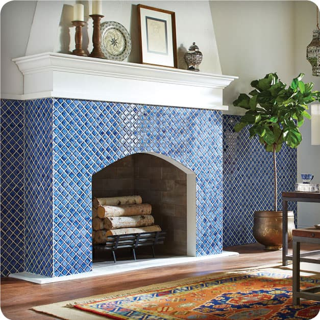 A living room fireplace tiled with the Merola Tile Hudson Tangier Sapphire which features unique reactive glaze in rich shades of blue.