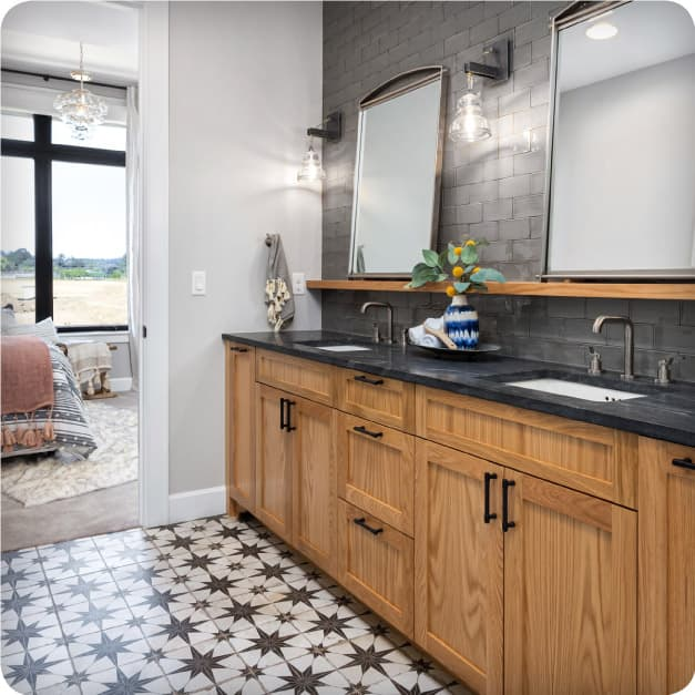 A luxurious modern bathroom is accented with the Merola's Kings Star Nero encaustic-look floor tile and Chester Grey handmade-look wall subway tile.