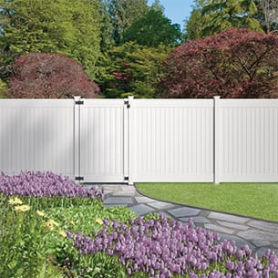 An image of the Dover fence installed along a backyard with a gate