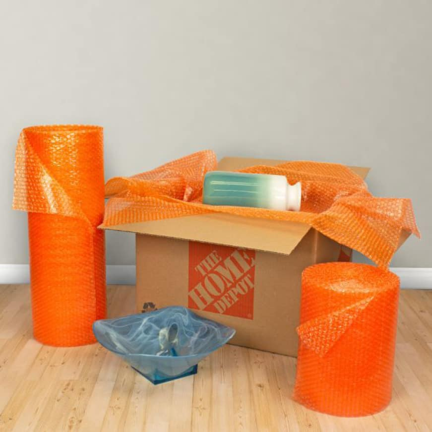 Bubble wrapping ceramic vase in medium moving box next to bubble wrap roll