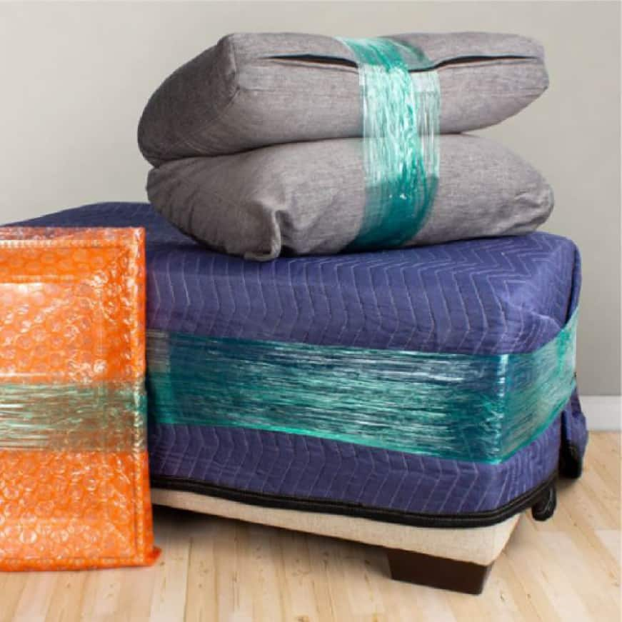Stretch film wrapped around mirror wrapped in bubble wrap, ottoman covered with moving blanket, and pillows