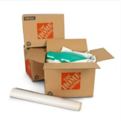 Small moving boxes filled with packing paper and a ceramic vase