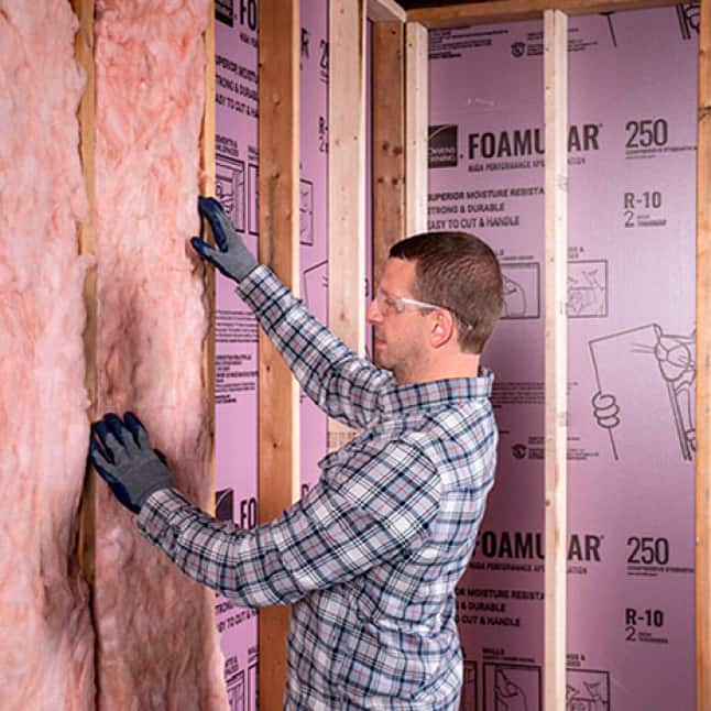 man installing fiberglas insulation  over Foamular