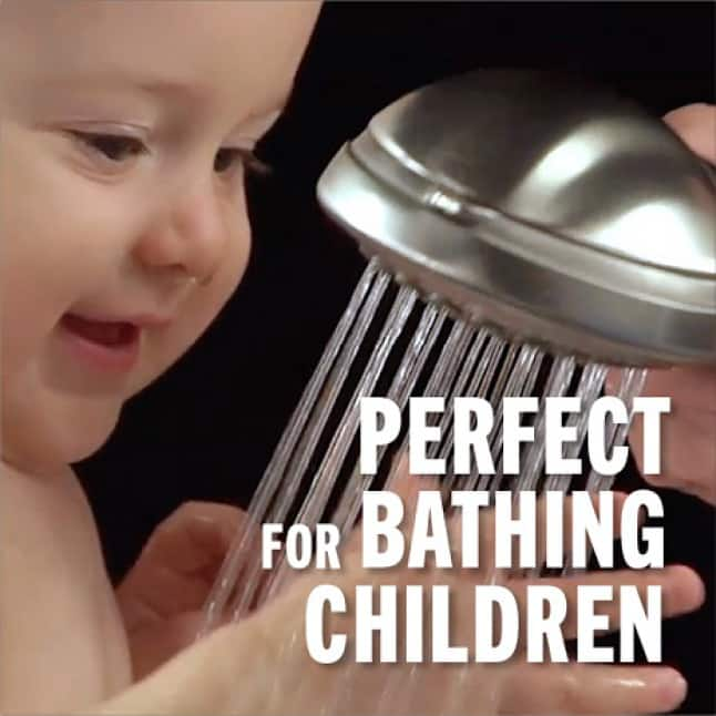Image is of a baby being bathed using the hand shower.