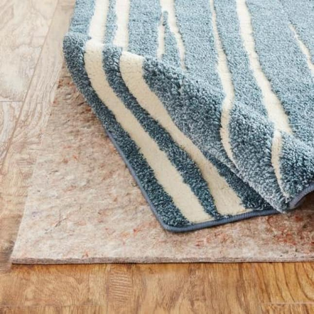 The image shows the top of a blue and cream, striped rug design, and the rug's corner is being rolled up slightly to expose the rug pad underneath.
