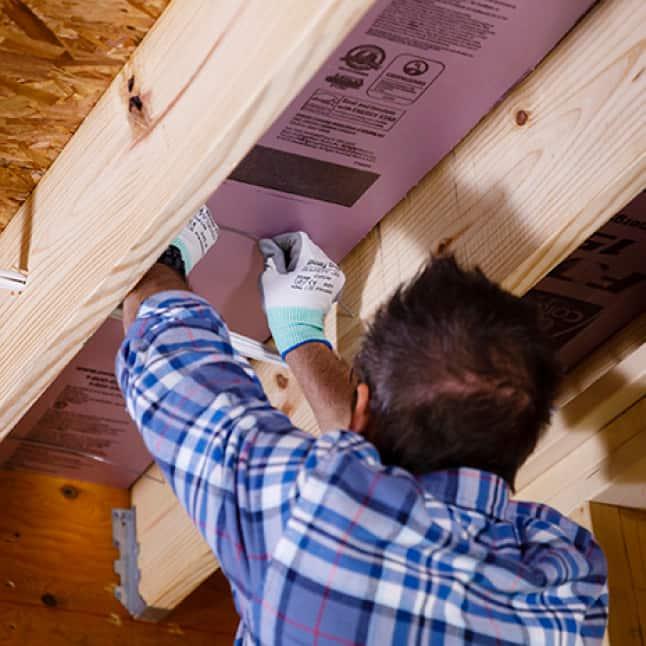 Man installing Foamular in a garage ceiling