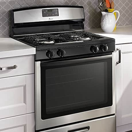An angled view of the stainless steel range shows the raised edge around the perimeter of the cooktop.