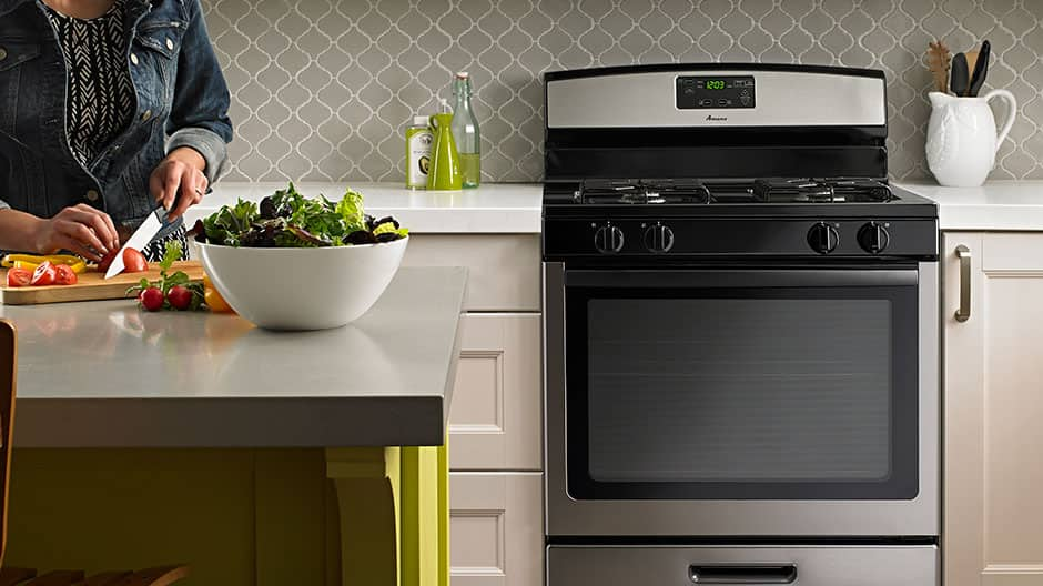 A stainless steel range in a kitchen set behind a woman at the kitchen island cutting tomatoes for a salad.