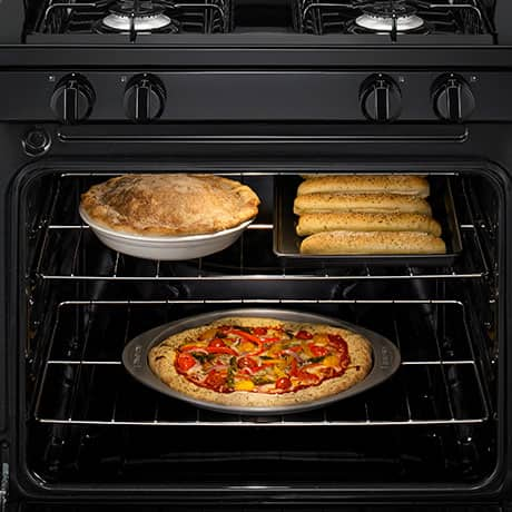 A pizza bakes on the bottom rack in the oven with a pie and breadsticks above it on the upper rack.