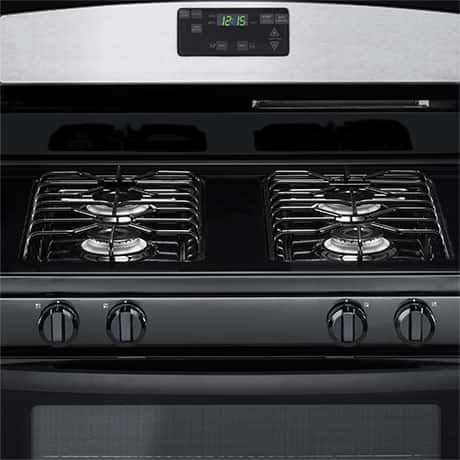 The black cooktop features four stainless steel sealed burners under black grates.