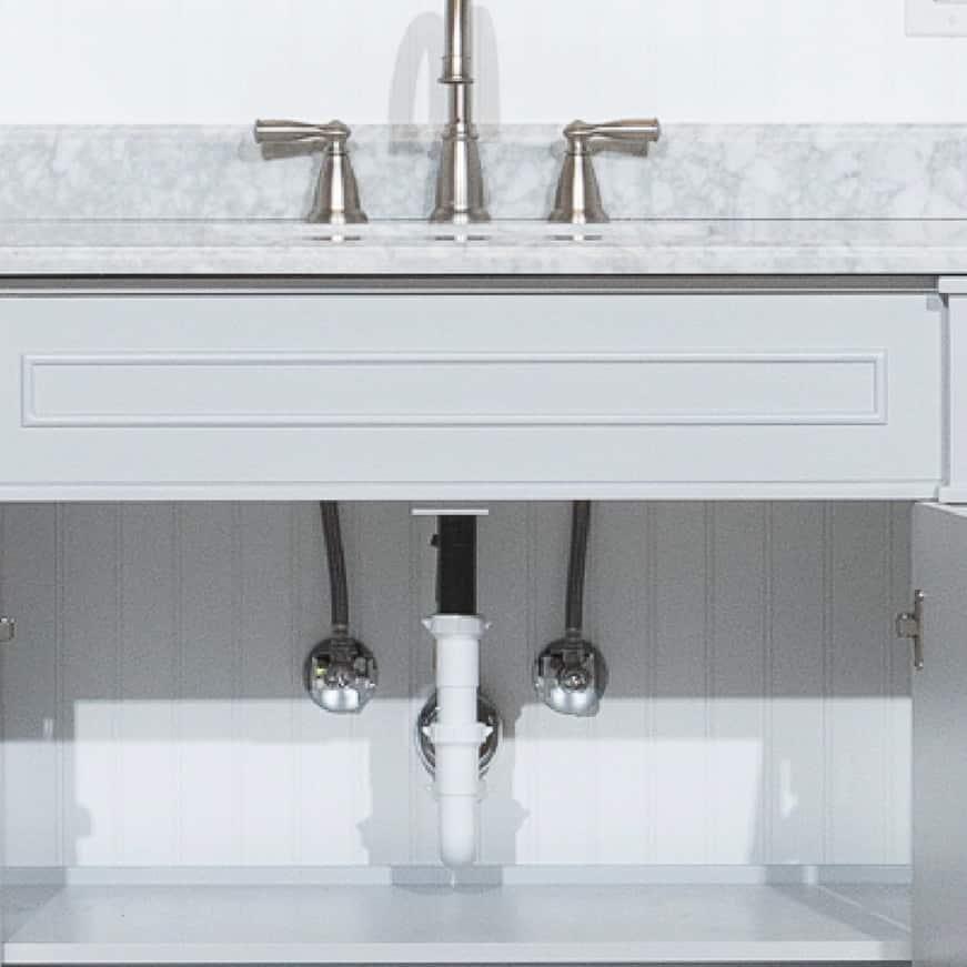 Plastic tubing underneath bathroom sink