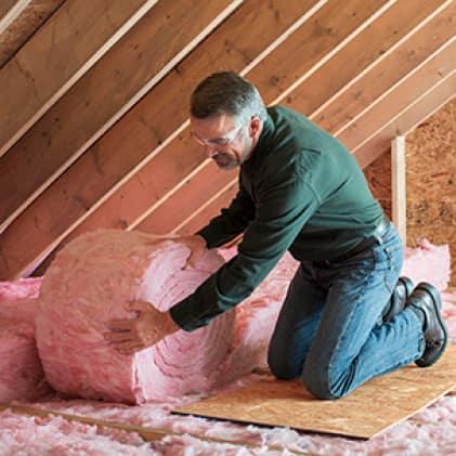 Man rolling pink fiberglass insulation in an attic