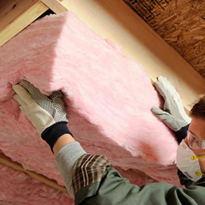 Man installing pink fiberglass insulation below a floor board