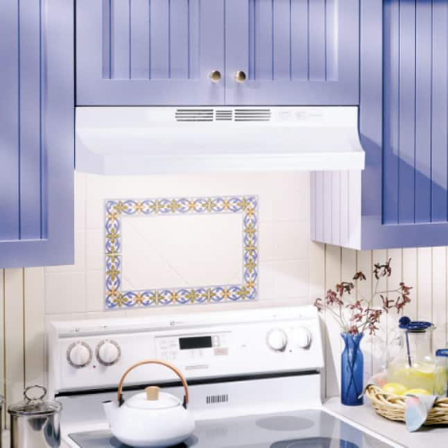 Image of the white range hood installed in a kitchen with a white stove and surrounded by lavendar cabinets.