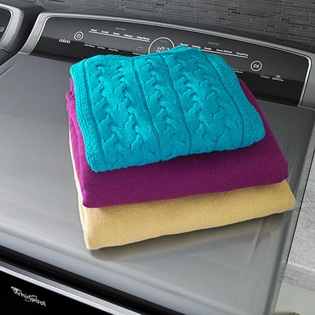 Three large, thick sweaters folded and stacked on top of the dryer.