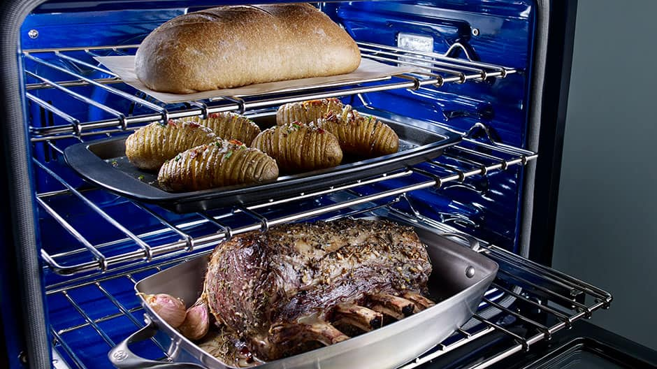 Angled view of open oven showing a large roast on the lower rack, scalloped potatoes on the middle rack and a loaf of bread baking on the upper rack.