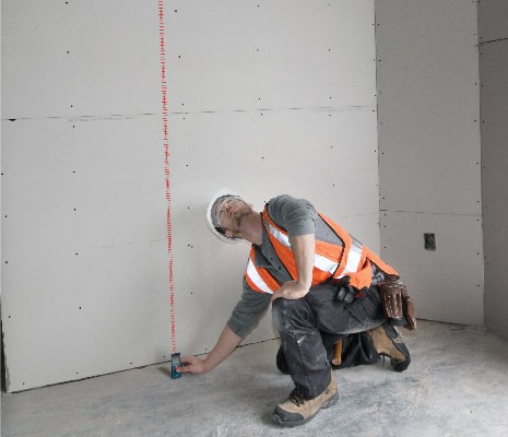 Bosch GLM 30 being used to take floor to ceiling measurement.