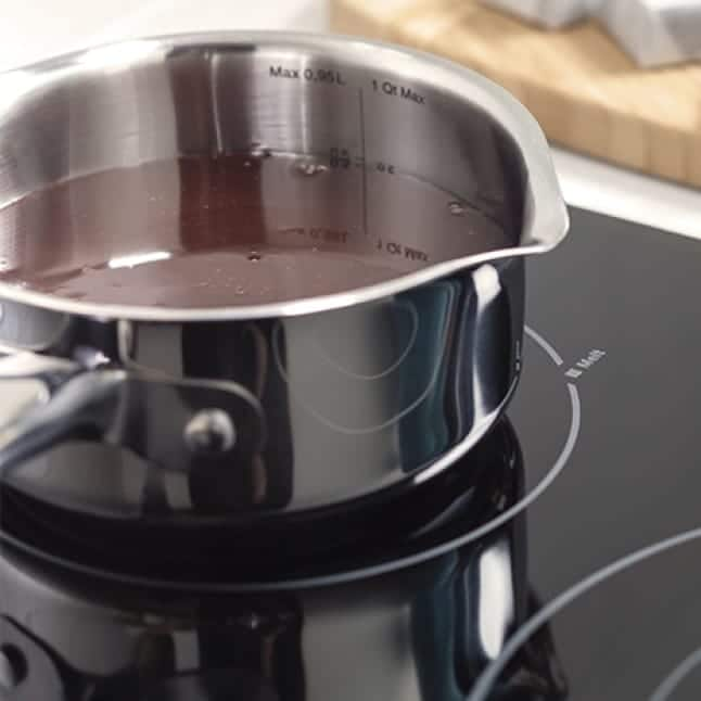 Chocolate in a pot is melted on the cooktop.