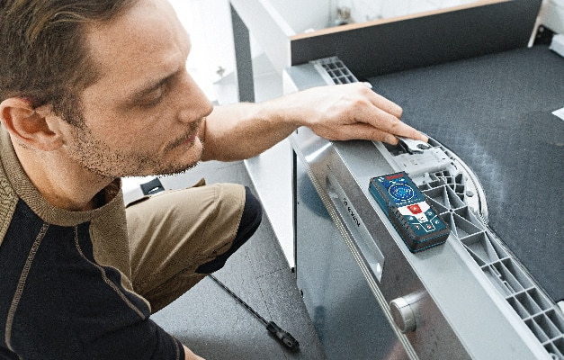 Bosch GLM 50 CX being used during dishwasher installation.