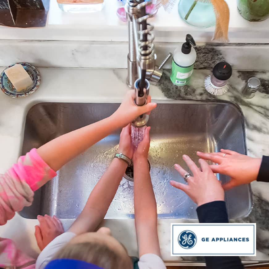 A family washes their hands together in the kitchen sink.