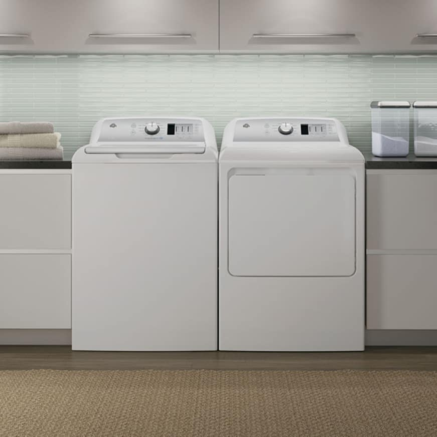 A conservative but modern laundry room. A GE washer and dryer sit at the center of the simple white room.