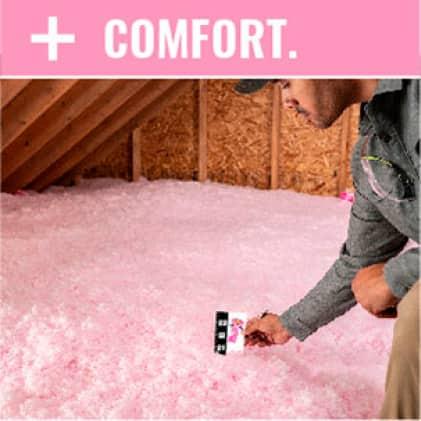man measuring AttiCat loosefill insulation in an attic
