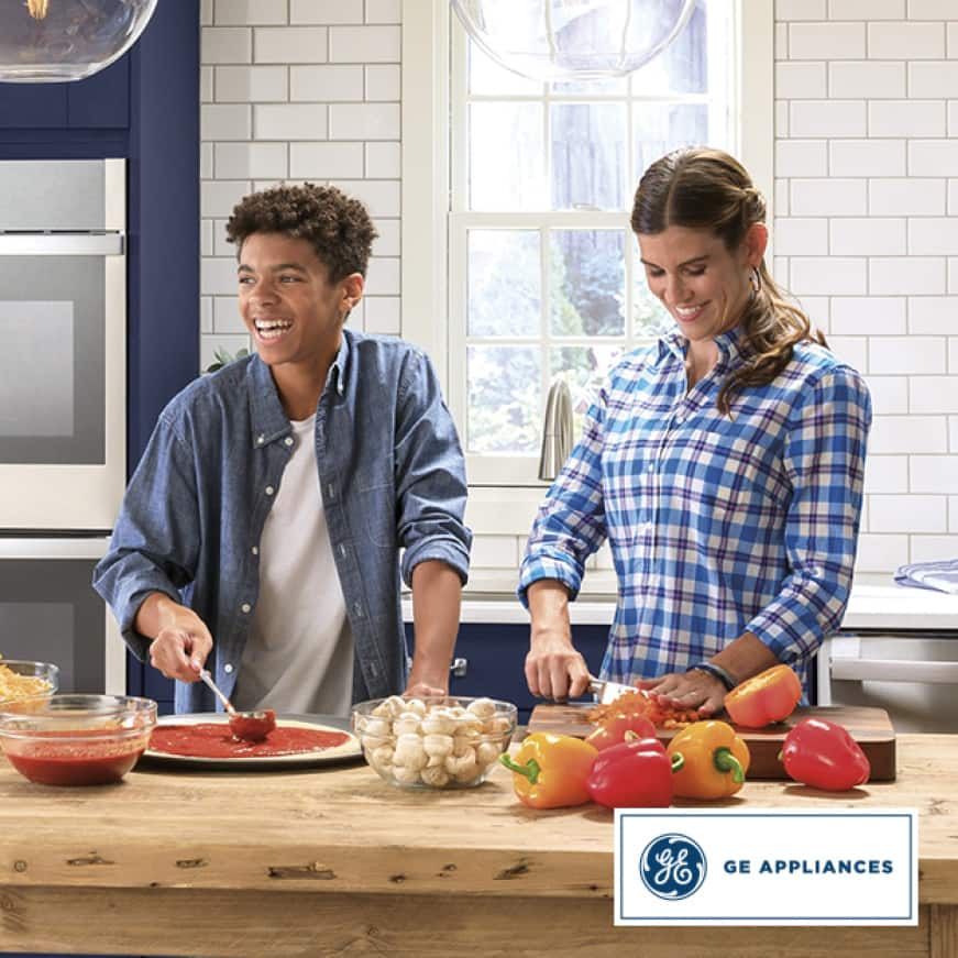 GE Appliances, the best bottom freezer refridgerator for food organizing. A woman chops peppers while a teenage boy stirs sauce on to a pizza crust.