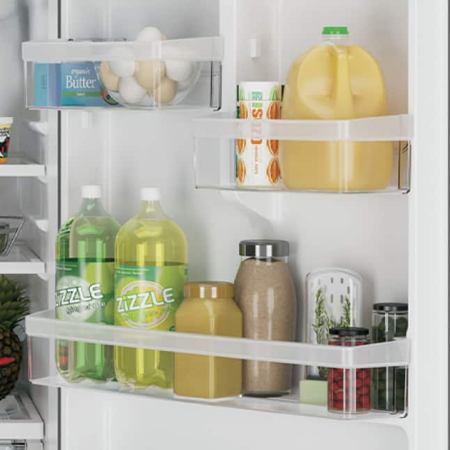 A variety of bottles, boxes, and jars of food and drink are neatly contained in the spacious door bins of the bottom freezer refridgerator.