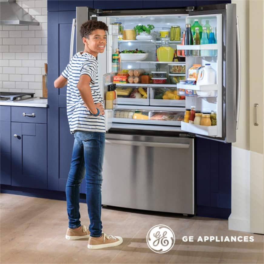 Talent standing in front of the open refrigerator filled with food.