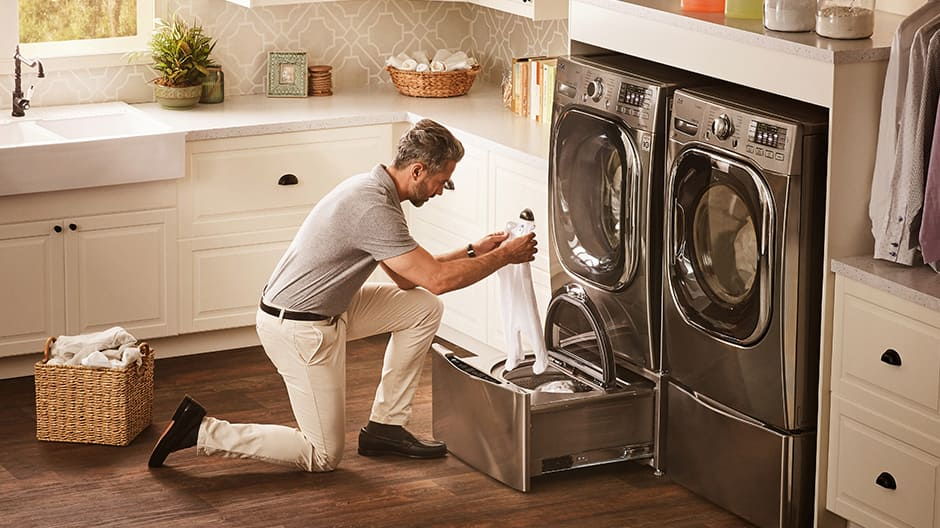 A man kneels in front of LG TWINWash in a bright laundry room, loading a babyÕs onesie into the LG SideKick Pedestal Washer