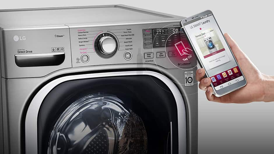 Close up of a hand holding a smartphone with the Smart Diagnosis App open in front of an LG washing machine