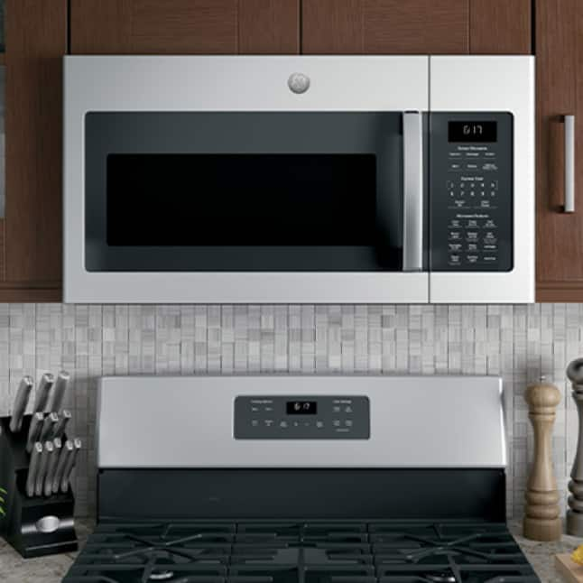 A microwave is installed over a range with a matching stainless-steel finish. Both are of similar width, showcasing the microwave's spacious capacity.