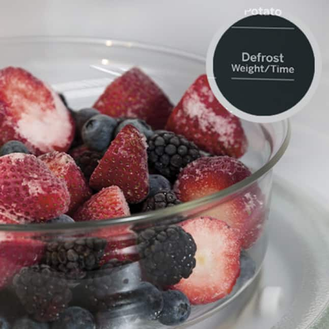 Frozen berries in a glass bowl defrost inside the microwave's cavity. A circular overlay shows the defrost button on the control panel.