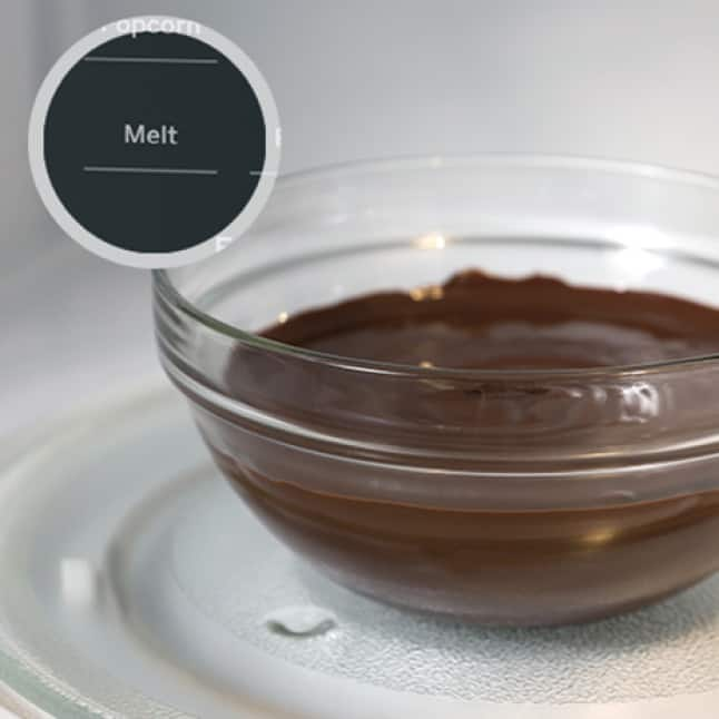 A glass bowl of freshly melted chocolate sits on the glass turntable in the microwave. A circular overlay shows the melt button on the control panel.