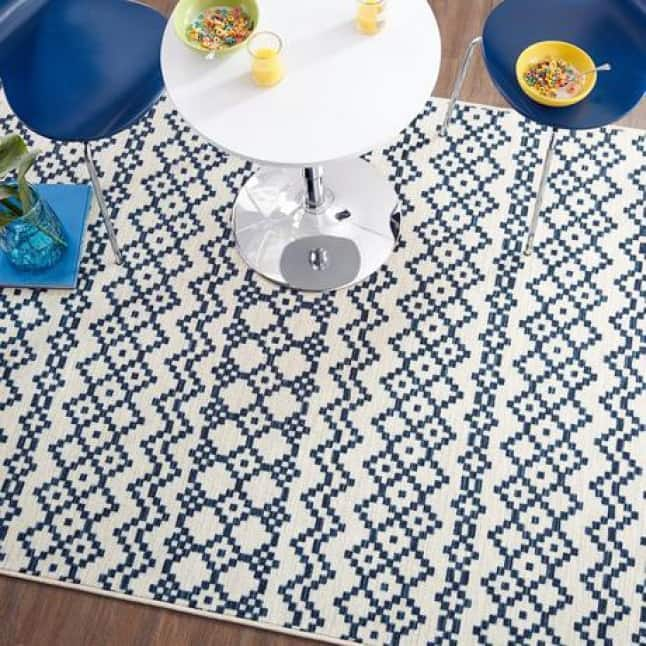 Image looks overhead a small breakfast nook with a blue & white, alternating striped geometric rug underneath everything.