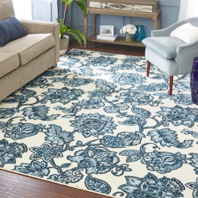 A blue hued, floral design rug sits in the center of a living room suite with a loveseat and armchair facing opposite to each other.