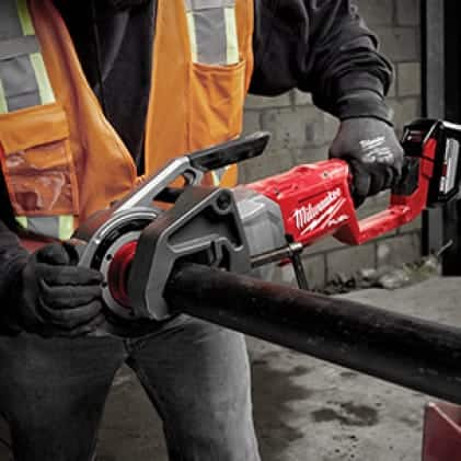 Man wearing a hi-vis vest and work gloves uses the M18 FUEL Pipe Threader on jobsite.