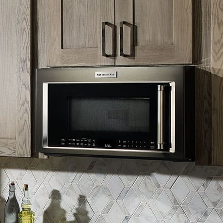 An image of an over-the range stainless steel microwave installed in light wood kitchen cabinets above a hexagonal patterned white backsplash.