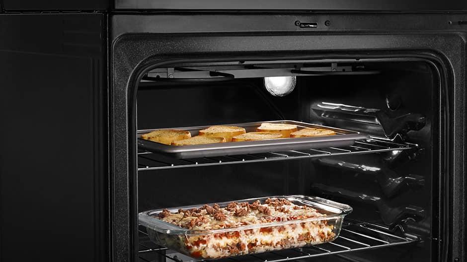 The oven door is open, revealing garlic bread baking on the upper rack and lasagna baking on the lower rack.