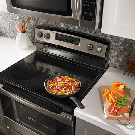 A skillet containing chicken and peppers for fajitas cooks on one of the range's four cooktop elements.