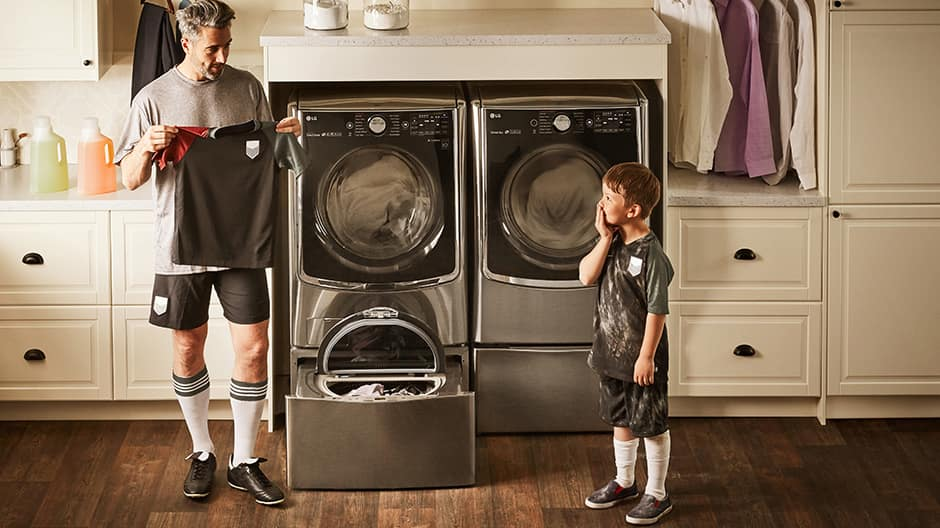 Sporty dad holds a dirty soccer uniform up to his son while they stand in front of the LG TWINWash with the LG SideKick Pedestal Washer