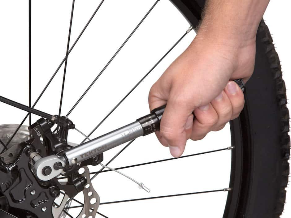 Image of TEKTON wrench tightening fastener on a bike