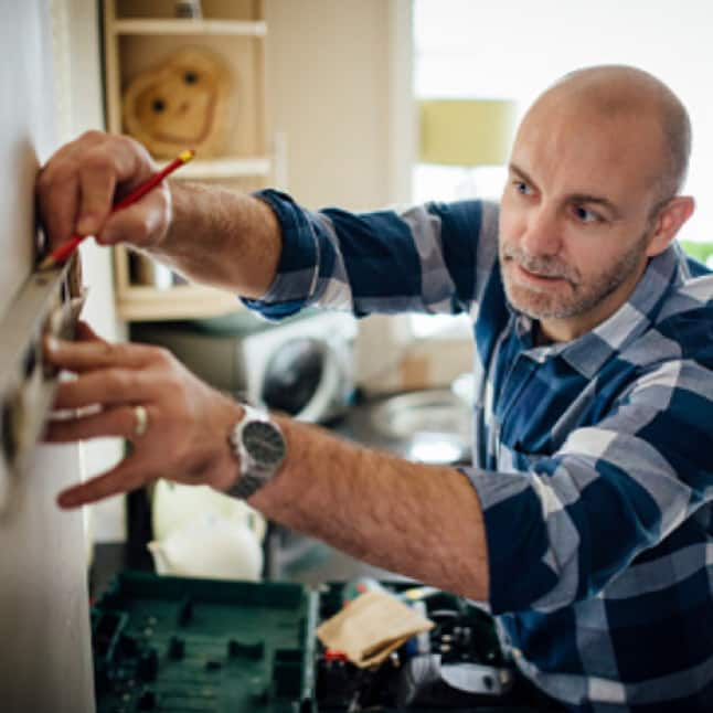Image of a man measuring the wall in a kitchen.