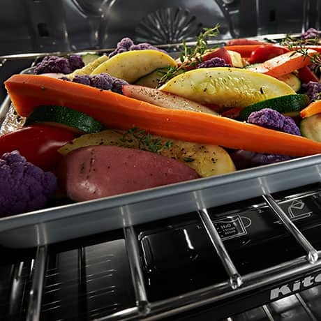A baking tray containing root vegetables sits in the oven on the steam rack.